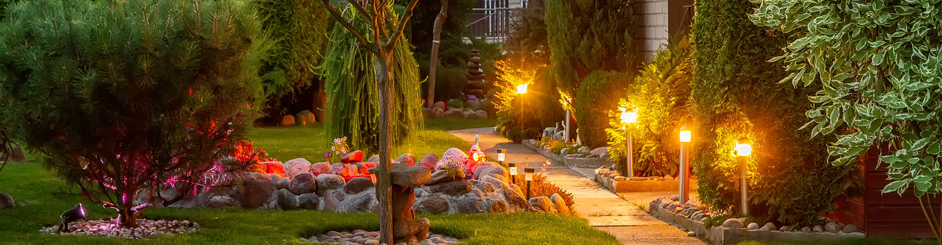 evening view of a manicured garden with outdoor lighting